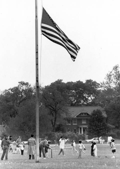 1990: Riverside Little Leagers practice T-ball while a flag flies at half-staff in tribute to three players killed in an accident earlier that month.