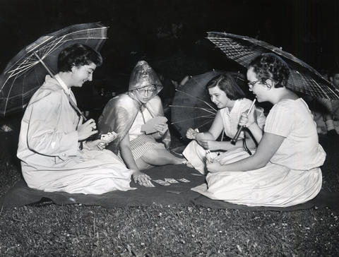 1959: Concertgoers shield themselves from rain as they play bridge at Ravinia's jazz festival.