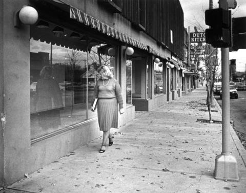 Virginia Lippig, president of Downtown Lombard Unlimited, Inc., a group of citizens and businessfolk supporting the revitalization of the older downtown Lombard area, walks past the closed Henderson, Inc. clothes store.