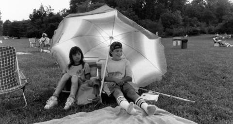 August 1988: Diane and Mark MacDonald bring their own shade to the Bluegrass Festival at Morton Arboretum.