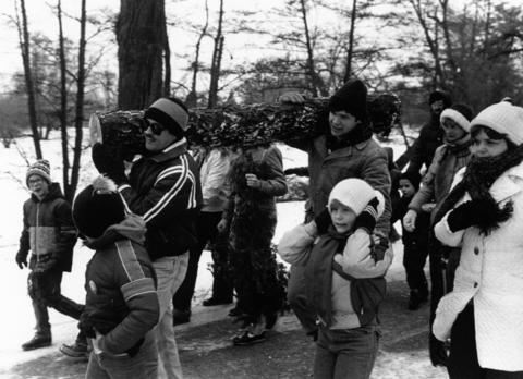 December 1988: The day after Christmas, participants in the annual yule log search carry their prize across Morton Arboretum grounds. The log is usually found within a half mile of the visitor's center. When the log is returned, it is cut in half. One half is used immediately to start a fire and the rest is saved for the next year's fire.