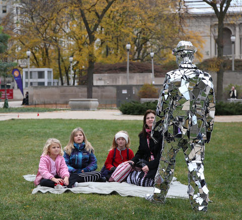 Corey Loeffelholz, dressed in a suit made with pieces of reflective material, approaches his family after posing for pictures with passers-by at the Sir Georg Solti Garden during the Halloween Gathering on Oct. 24, 2015, in Chicago.