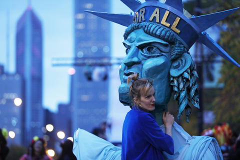 A woman holds a Statue of Liberty costume before marching in the Halloween Gathering Parade on South Columbus Drive onOct. 24, 2015, in Chicago.