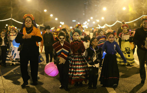 Logan Martinez, 8, center left, and Chanell Hernandez, 10, center, march with schoolmates and teachers from Edwards Elementary School in the Halloween Gathering parade on South Columbus Drive on Oct. 24, 2015, in Chicago.