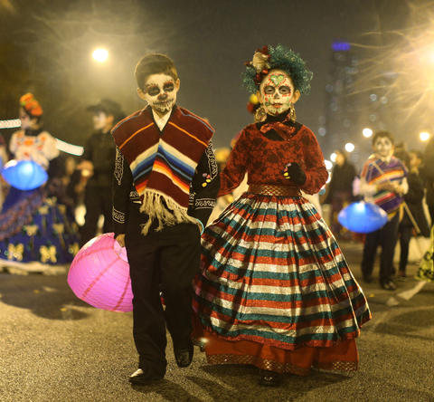 Logan Martinez, 8, left, and Chanell Hernandez, 10, march with schoolmates and teachers from Edwards Elementary School in the Halloween Gathering parade on South Columbus Drive on Oct. 24, 2015, in Chicago.