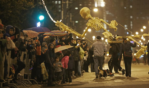 Puppeteers maneuver an oversized skeleton puppet over the crowd during the Halloween Gathering Parade on South Columbus Drive onOct. 24, 2015, in Chicago.