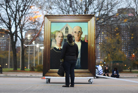 """A woman stops to view an oversized replica of Grant Wood's """"American Gothic"""" before the Halloween Gathering Parade on South Columbus Drive onOct. 24, 2015, in Chicago."""