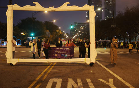 A group of visual artists march, framed by an oversized painting frame, during the Halloween Gathering Parade on South Columbus Drive onOct. 24, 2015, in Chicago.