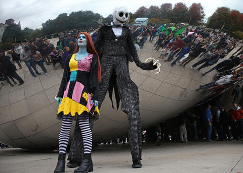"""Malinda and Kyle Mathis, dressed as characters from the film, """"Nightmare Before Christmas,"""" stand in front of people wanting to pose for pictures with the couple at the Cloud Gate sculpture in Millennium Park during the Halloween Gathering on Oct. 24, 2015, in Chicago."""