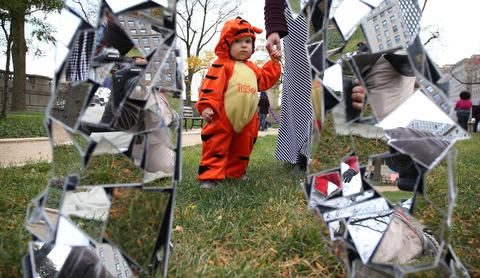 One-year-old Amara Stoppa views a man dressed in a suit made with reflective pieces at Sir Georg Solti Garden during the Halloween GatheringonOct. 24, 2015, in Chicago.