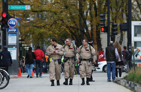 """Mark Hagan, from left, Joe Gagliano and Jason Staadt, dressed as the titlecharacters in""""Ghostbusters,"""" walk south on the 300 block of South Michigan Avenue before marching in the parade at the Halloween Gathering on Oct. 24, 2015, in Chicago."""