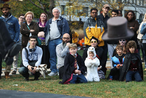 """A top hat flies offstage as children and adults watch a performance by """"Sammy Tramp"""" at Sir Georg Solti Garden during the Halloween GatheringonOct. 24, 2015, in Chicago."""