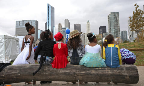 Children in the Joffrey Ballet Community Engagement Dancers group wait on a log bench after performing at Maggie Daley Park during the Halloween GatheringonOct. 24, 2015, in Chicago.