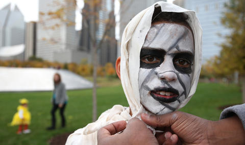 Jacob Pinckney, 9, gets help with his mummy costume fromhis father at Maggie Daley Park during the Halloween GatheringonOct. 24, 2015, in Chicago.