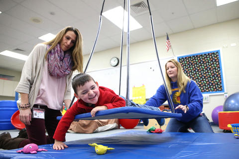 Matthew Erickson uses a swing to grab objects with therapist Kathy Murphy, right, and teacher's aide Nicole Simons during preschool Nov. 18, 2015, in Lake in the Hills. Matthew is celebrated as a survivor after reaching a pivotal mark in August — having gone three years without chemotherapy.