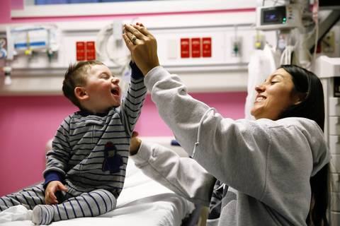 Sue Erickson high-fives her nearly 2-year-old son, Matthew Erickson, as he's prepped for an MRI brain scan on Dec. 4, 2013, at Lurie Children's Hospital in Chicago.