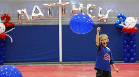 Nolan Erickson, 6, swings a balloon around at his brother Matthew Erickson's 2nd birthday party Dec. 7, 2013, at Elgin Community College.