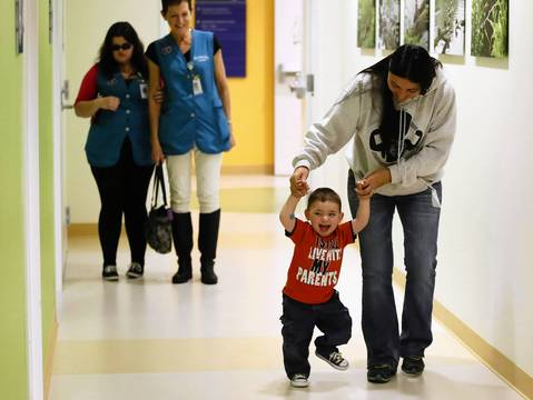 Sue Erickson helps her 1-year-old son, Matthew, walk to his doctor after a brain scan Dec. 4, 2013, at Lurie Children's Hospital in Chicago.