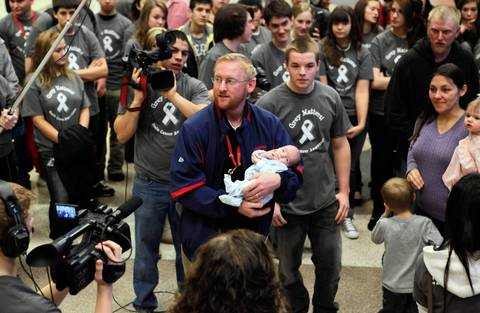 Ben Erickson holds his son Matthew on Jan. 26, 2012, as students from South Elgin High School present the Erickson family with $5,000 to help baby Matthew fight a brain tumor.