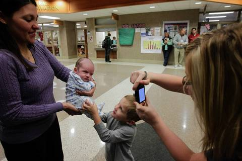 "A South Elgin High School student takes a picture of Nolan Erickson, 5, baby Matthew Erickson and their mom, Sue Erickson, on Jan. 26, 2012. When parents Sue and Ben Erickson heard the news from the oncologist that their son's organs were functioning normally and, aside from a malignant tumor, he was healthy, Sue said, '""We just looked at each other and said, ''If there''s any chance at all, we have to give it to him.'""'"""