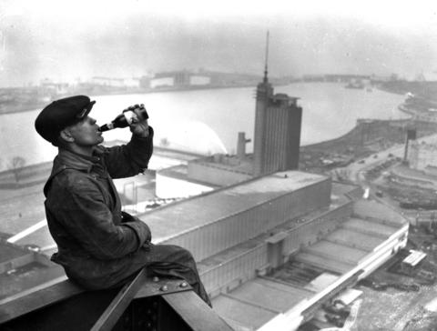 An iron worker, perched on the west tower of the Sky Ride, drinks an Edelweiss beer during construction of the World's Fairin1933. When completed, the Sky Ride consisted of two, 625-foot-tall towers that straddled the lagoon between Northerly Island and the lakefront. The ride had rocket-shaped cars that transported 36 fair-goers across the lagoon at a time.