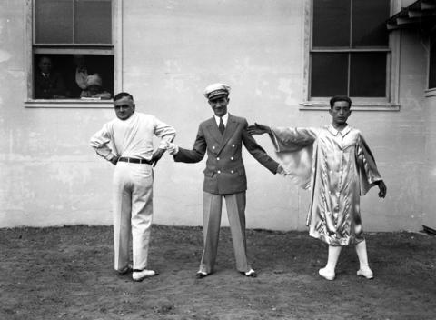 """Announcer Eddie Lovett, center, shows off Martin Laurello, the """"Revolving Head,"""" left, and Demetrio Ortis, the """"Human Twister"""", at Ripley's Odditorium on June 7, 1934. Robert Ripley first displayed his collection of oddities to the public at the World'sFair."""