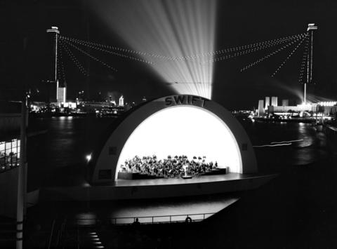 """The floating Swift Theater lights up the night as the Chicago Symphony Orchestra plays the second of two daily concerts July 7, 1934. """"The Swift Theater is part of the Swift Bridge at 23rd Street, which connects the mainland with Northerly Island,"""" the Tribune explained. """"The open air auditorium will seat about 1,700 patrons, who are separated from the music shell by an expanse of 64 feet of water."""" The Sky Ride can be seen in the background."""