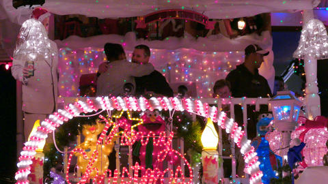 Guests embrace at one of the homes that were illuminated during the annual lighting of Christmas lights in Hampden for the holiday season.