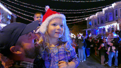 Iris Fisher, 3-1/2, held by her father, Matt Fisher, catches sight of Santa Claus, who arrives by pickup during the annual lighting of Christmas lights in Hampden for the holiday season.