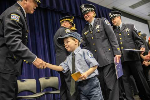 Edward Stachura, 4, gets a handshake from police Superintendent Garry McCarthy as his mother, Officer Melissa Stachura, receives an award at a monthly commendation ceremony on March 18, 2014.