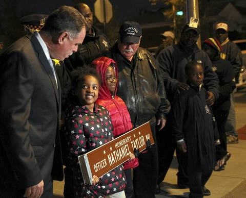 Chicago police Superintendent Garry McCarthy gets a smile from Naomi Taylor, 9, on Nov. 9, 2012, as a street sign is dedicated in honor of the girl's father, fallen police Officer Nathaniel Taylor. The officer was fatally shot Sept. 29, 2008, while serving a search warrant.