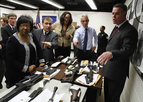 Chicago police Superintendent Garry McCarthy, right, Mayor Rahm Emanuel and others look at confiscated guns Jan. 8, 2013, after an announcement of the revitalization of the community policing program.