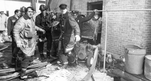 February 1973: Firefighters carry the body of one of three volunteer firefighters killed fighting a blaze that destroyed the Ben Franklin Variety Store in downtown Palatine.