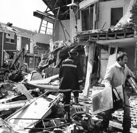 April 1976: A firefighter examines rubble while a rescue worker carries damaged items where six people were injured after a natural gas explosion at an apartment building in Palatine.