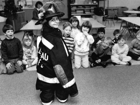November 1987: Nisha Goyal delights her classmates at Marion Jordan School in Palatine by almost disappearing into the gear of a visiting firefighter.