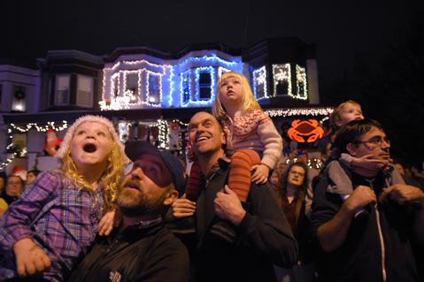 From left, Iris Fisher, 3 1/2, with her father, Matt Fisher, and Frankie Riley, 3, sits atop her father, Mike Riley, and Miles Carscadden, 3-1/2, sits on Lucas Carscadden, all of Baltimore, who react during the annual lighting of Christmas lights in Hampden for the holiday season.
