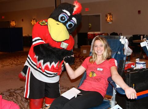 Chicago Blackhawks mascot Tommy Hawk comforts Angie Benton of Naperville during her blood donation at the Dec. 19 LifeSource Holiday Blood Drive at The Westin O'Hare. More than 200 pints were collected throughout the day.
