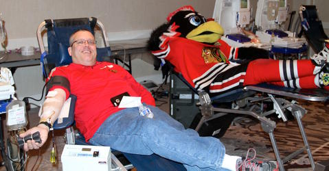 Jim Hirsch of Gurnee donates blood next to Chicago Blackhawk mascot Tommy Hawk during the annual LifeSource Holiday Blood Drive with the Blackhawks December 19 at The Westin O'Hare in Rosemont.