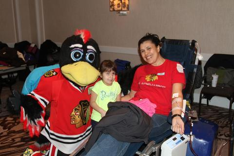 Chicago Blackhawks mascot Tommy Hawk visits with and Dulce Caro (center) and Beatrice Cano of Des Plaines during the annual LifeSource Holiday Blood Drive with the Blackhawks December 19 at The Westin O'Hare in Rosemont.