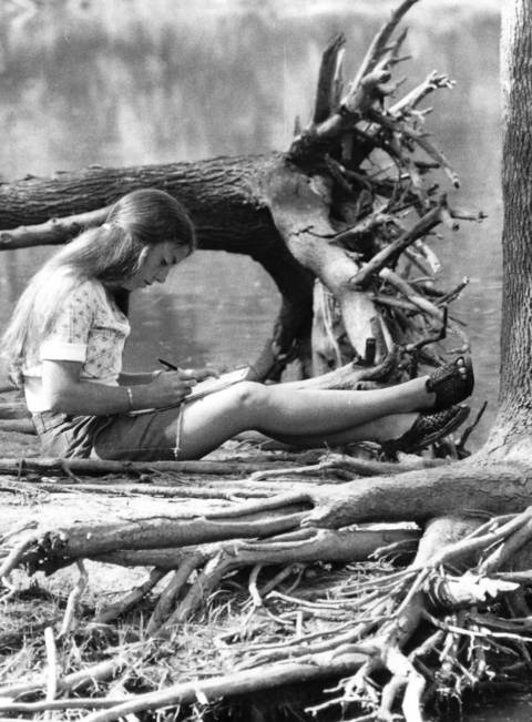 A woman catches up on her letter writing while relaxing in a forest preserve in Winnetka in 1974.