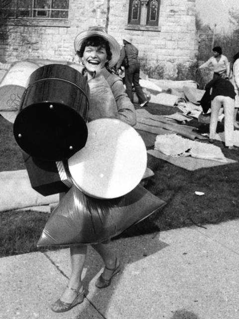 Loaded with boxes filled with second-hand hats, a delighted Carol Cervantes walks away from the Winnetka Congregational Church rummage sale in 1984.