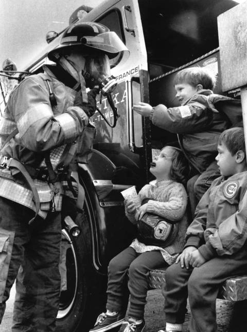 A Winnetka firefighter shows off his gear to Nick Piepmeier (top), Gwennie Poor and Darren Angell in an attempt to show that a firefighter may look scary all dressed up, but is a friend during an emergency in 1988.