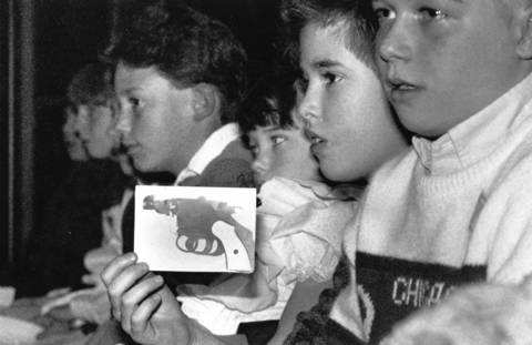 "A young boy holds a photo of a ""Saturday Night Special,"" a low-cost revolver, during a Winnetka board meeting covering a possible handgun ban in 1989."