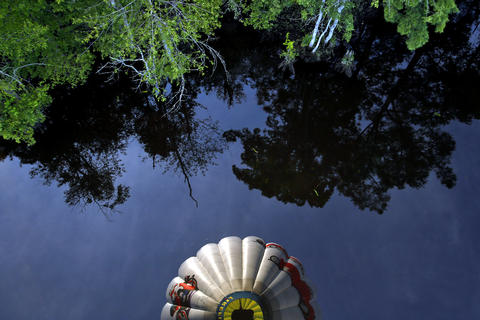 Pilot Reed Basley's hot air balloon is reflected in a body of water near Lanexa Monday evening.