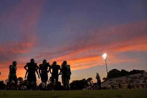 Kecoughtan players huddle as the sun sets during Thursday's game against Gloucester at Darling Stadium on August 27, 2015.