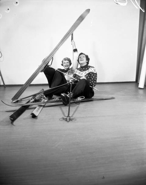 """Miss Nancy Bye of Chicago and Miss Janet Fancher of Evanston, shown in a """"spill"""" during a practice session on skis in the studio on Dec. 5, 1956."""
