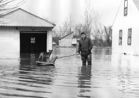 April 1960: Rusty gets a ride on a raft on a flooded Victory Parkway in Addison, courtesy of his owner, Darrel Featherly.
