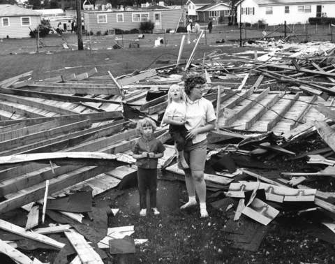 May 1965: Mrs. Wilmer Stahlmann (first name not given) and her daughters, Cheryl, 5, and Sharon, 3, survey their yard at 4N304 Mill Rd. in Addison, where a roof landed in tatters after a tornado.