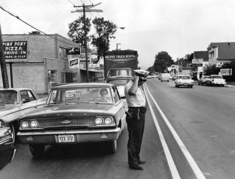 August 1965: Addison police officer James Carolis views lines painted in the wrong place on Lake Street. The mistake created three eastbound lanes, but only one westbound lane.