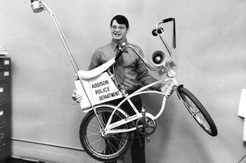 "December 1971: Addison Det. Charles Gruber shows off ""Mike the Bike,"" a ""talking"" bicycle. The bicycle has a recorded message with a speaker mounted between the handlebars. It is used to promote bicycle safety."